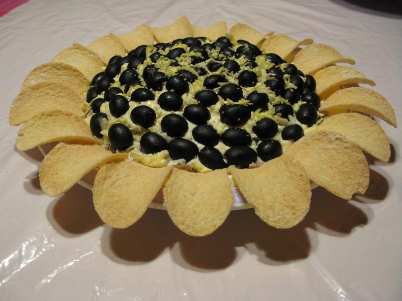 Для украшения салата, используйте тертый сыр, оливки и чипсы, которые будет на месте лепестков подсолнуха.