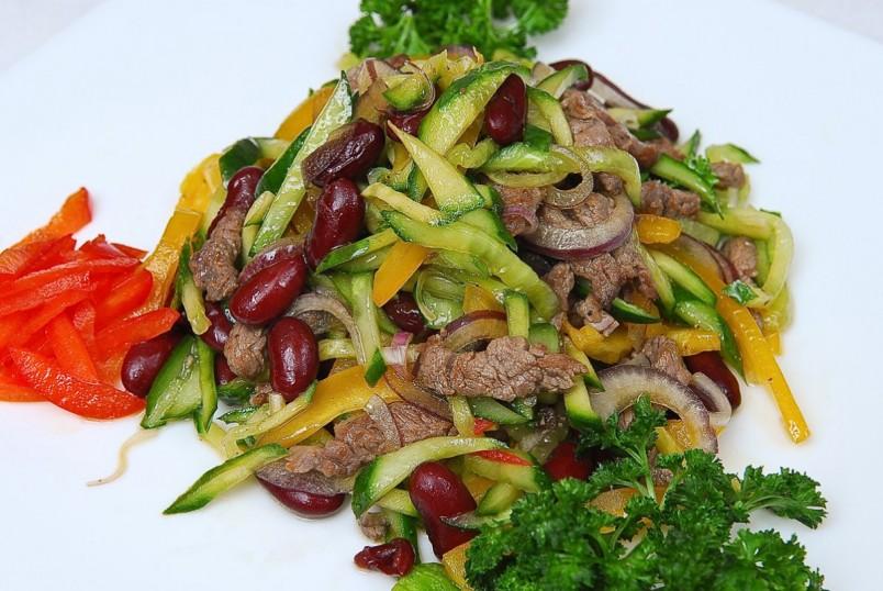 Горячий салат с фасолью и мясом обладает колоритным вкусом и отлично подойдет для украшения стола.