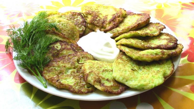 Оладьи из кабачков с зеленью лучше подавать со сметаной.